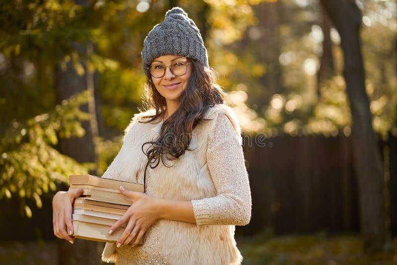 La mujer en un casquillo y vidrios está sosteniendo una pila de libros en el fondo del bosque del otoño fotografía de archivo
