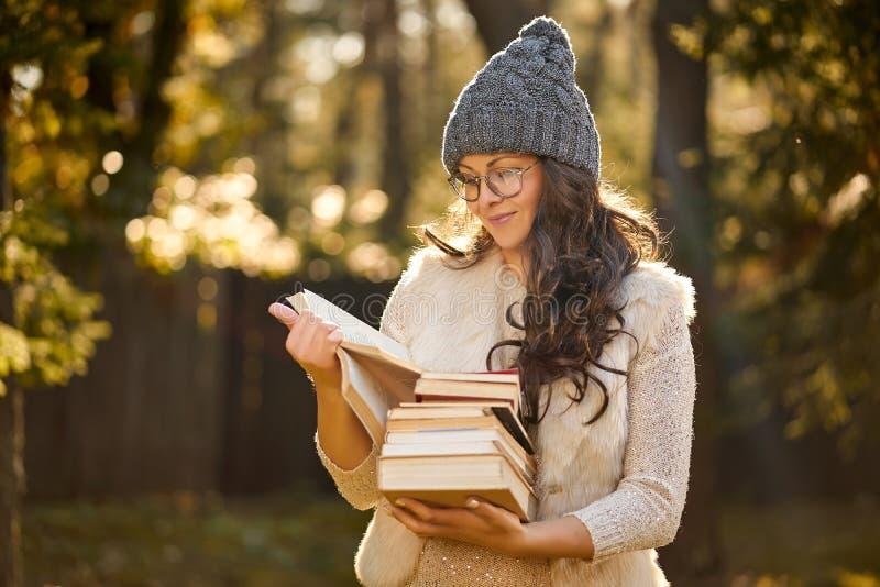 La mujer en un casquillo y vidrios está sosteniendo una pila de libros en el fondo del bosque del otoño imágenes de archivo libres de regalías