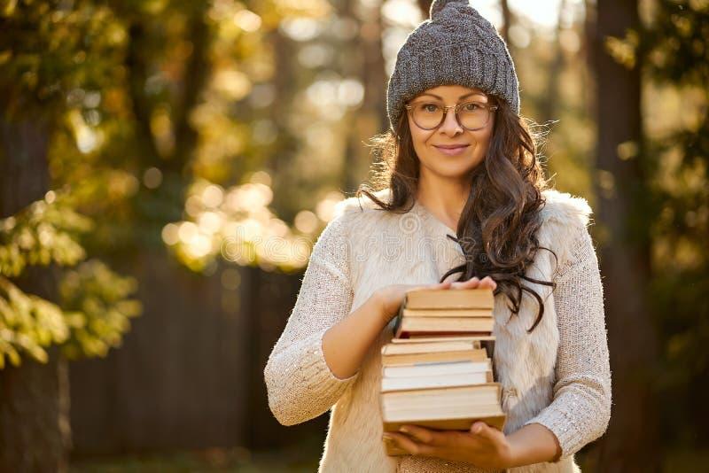 La mujer en un casquillo y vidrios está sosteniendo una pila de libros en el fondo del bosque del otoño foto de archivo