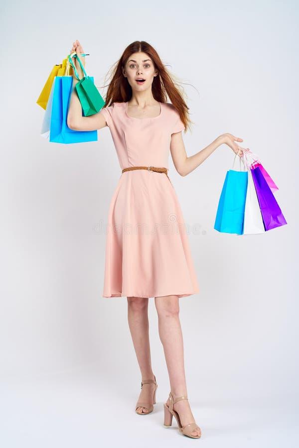La mujer en un fondo blanco sostiene las bolsas de papel, compras, compras, entretenimiento imagenes de archivo