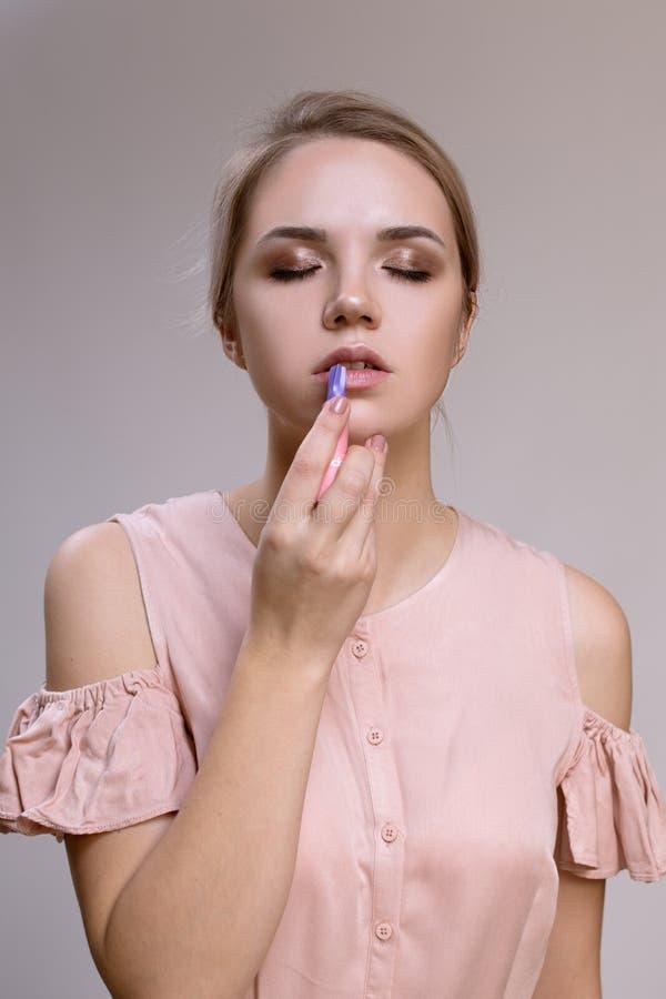 La mujer en un fondo gris pinta los labios con la barra de labios fotografía de archivo libre de regalías