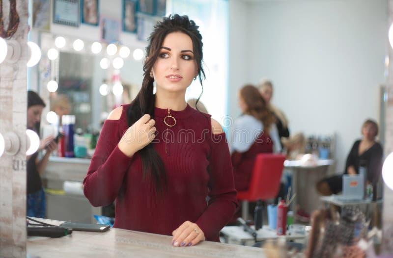 La mujer en un salón de belleza mira su reflexión en el espejo en su maquillaje y peinado foto de archivo libre de regalías