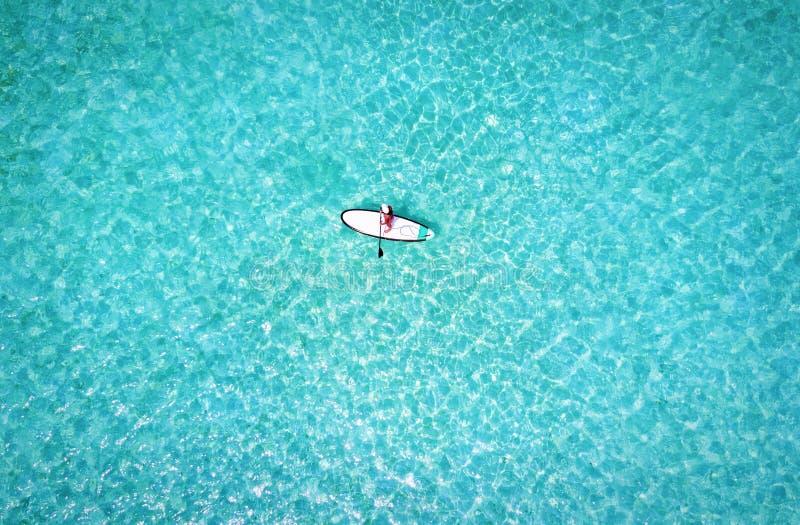 La mujer en un soporte encima del barco de paleta sobre la turquesa riega foto de archivo libre de regalías