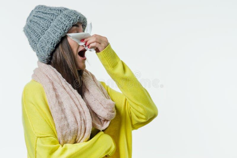 La mujer en un suéter, sombrero hecho punto, bufanda estornuda con un pañuelo Estación del frío común, virus, rinitis fotografía de archivo libre de regalías