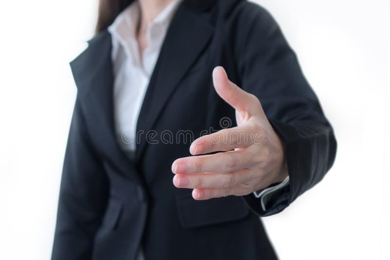 La mujer en un traje de negocios lleva a cabo hacia fuera su mano para un apretón de manos en el fondo blanco fotos de archivo