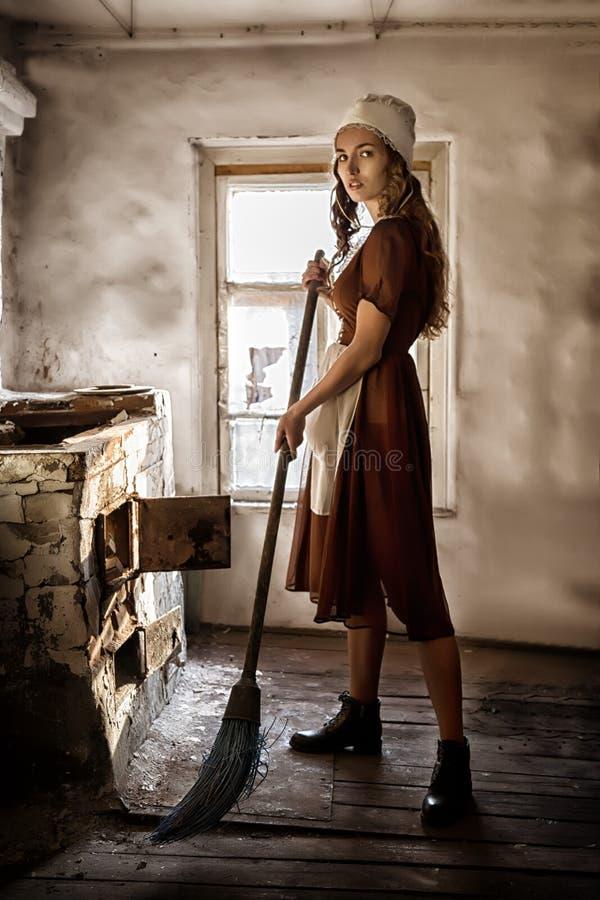 La mujer en un vestido rústico barre el piso de madera en la cocina foto de archivo libre de regalías