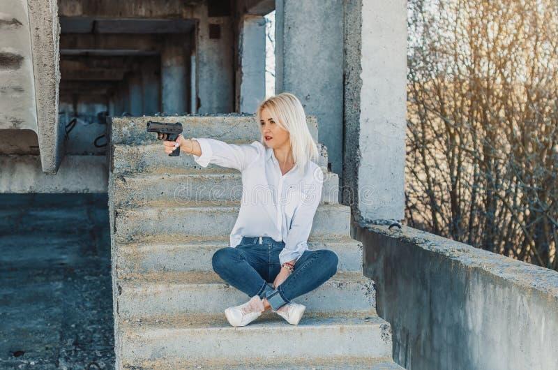 La mujer en una camisa blanca se sienta en pasos concretos, tira un arma foto de archivo libre de regalías
