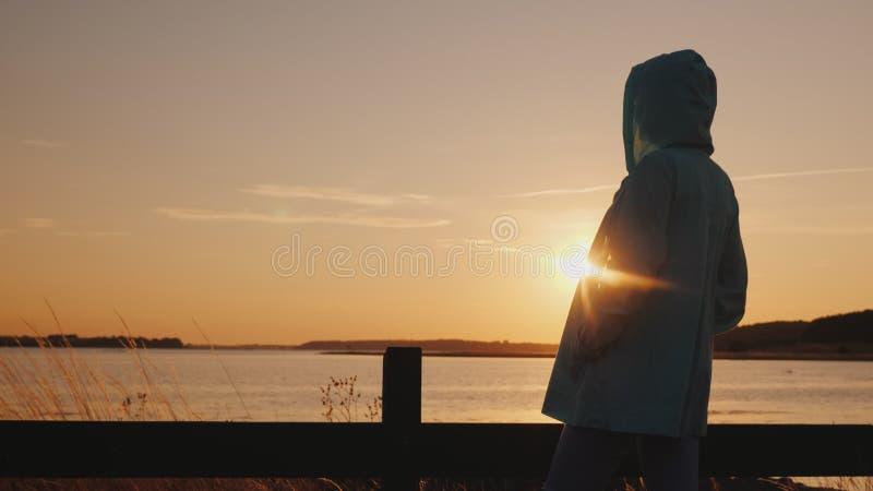 La mujer en una chaqueta del otoño con una capilla admira la puesta del sol sobre el lago foto de archivo