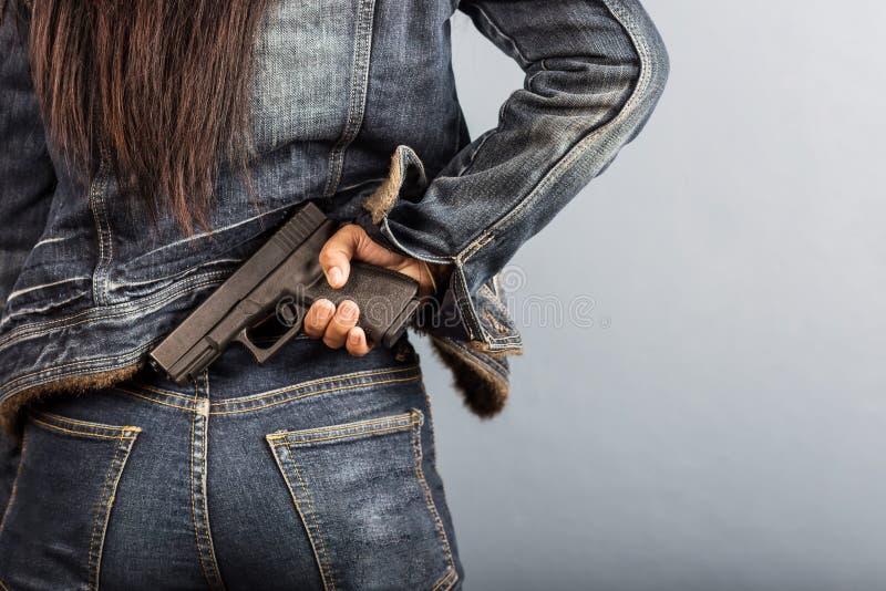 La mujer en vaqueros está sosteniendo un arma fotografía de archivo