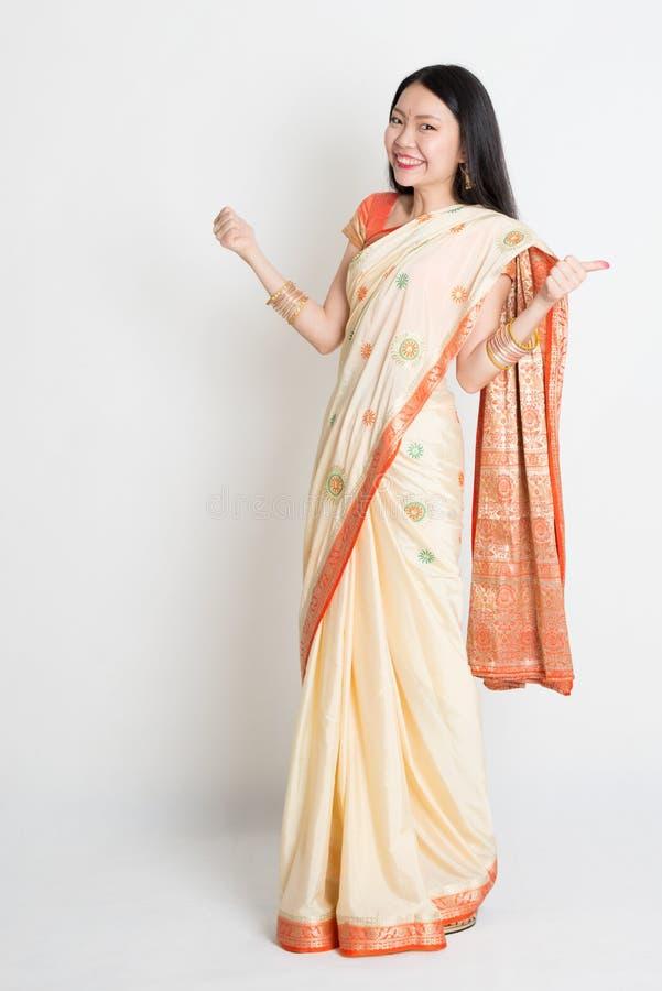 La mujer en vestido indio de la sari manosea con los dedos para arriba imágenes de archivo libres de regalías