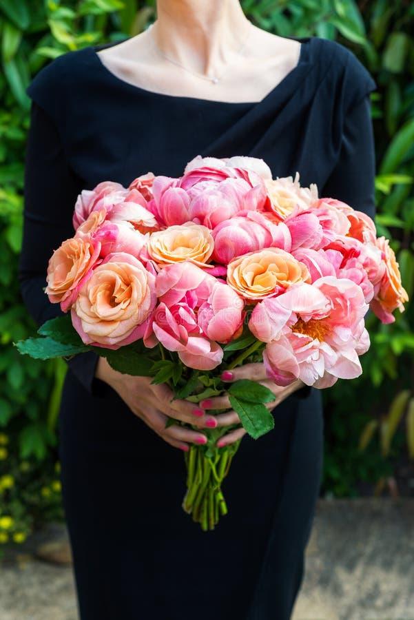 La mujer en vestido negro está sosteniendo el manojo de peonías y de rosas rosadas imágenes de archivo libres de regalías