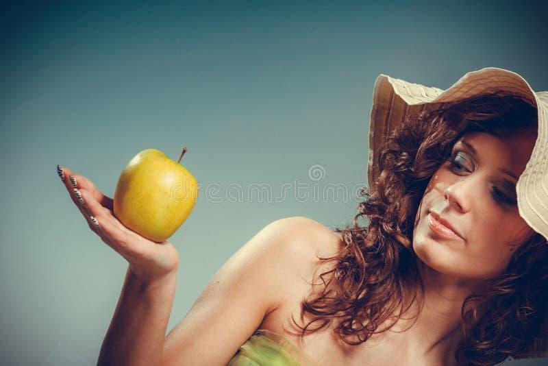 La mujer en vestido y el sombrero sostienen la manzana amarilla foto de archivo
