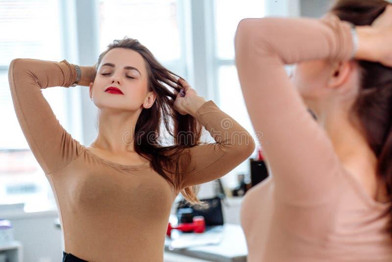 La mujer endereza el pelo delante del espejo imágenes de archivo libres de regalías