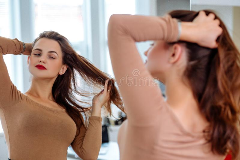La mujer endereza el pelo delante del espejo fotos de archivo