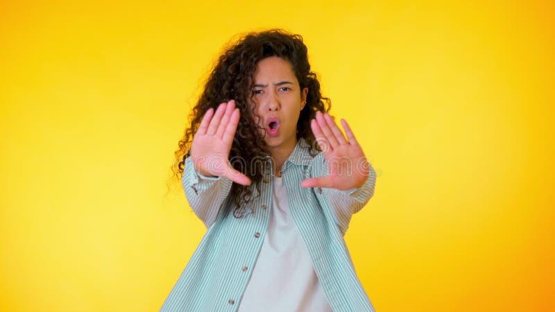 La mujer enfadada enojada que aumenta la mano hasta dice no la parada Mirada esc?ptica y desconfiada, sintiendo enojada en alguie foto de archivo