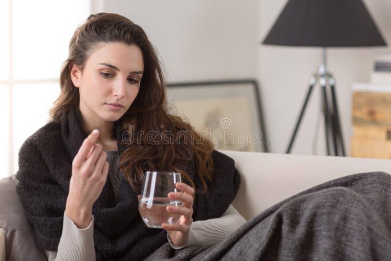 La mujer enferma malsana toma la píldora con el vidrio de agua imagenes de archivo