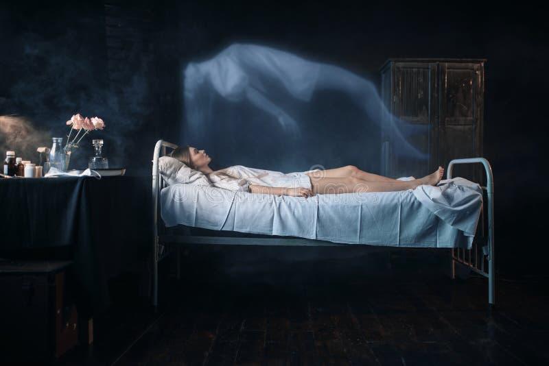 La mujer enferma que miente en la cama de hospital, alma deja el cuerpo fotos de archivo libres de regalías
