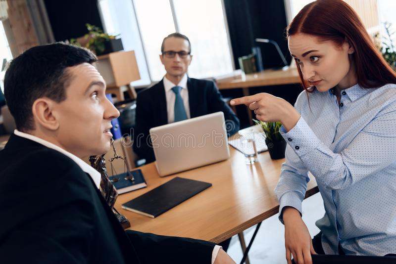 La mujer enojada Redheaded discute con el hombre adulto en oficina del ` s del abogado de divorcio foto de archivo libre de regalías