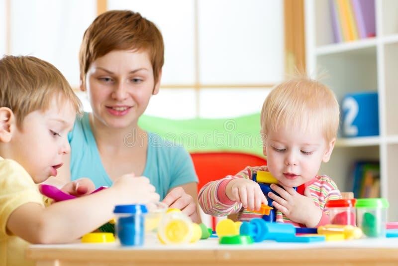 La mujer enseña los niños a artesanía en la guardería o el playschool imagenes de archivo