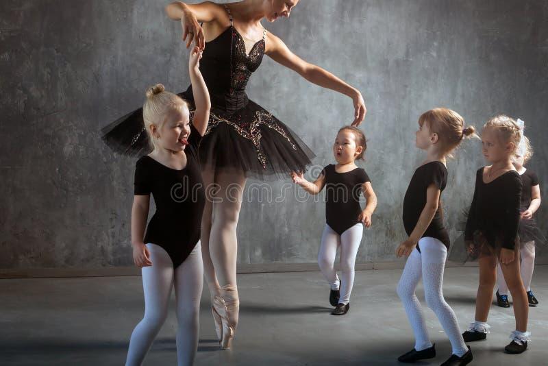 La mujer enseña a muchachas a bailar ballet imagenes de archivo
