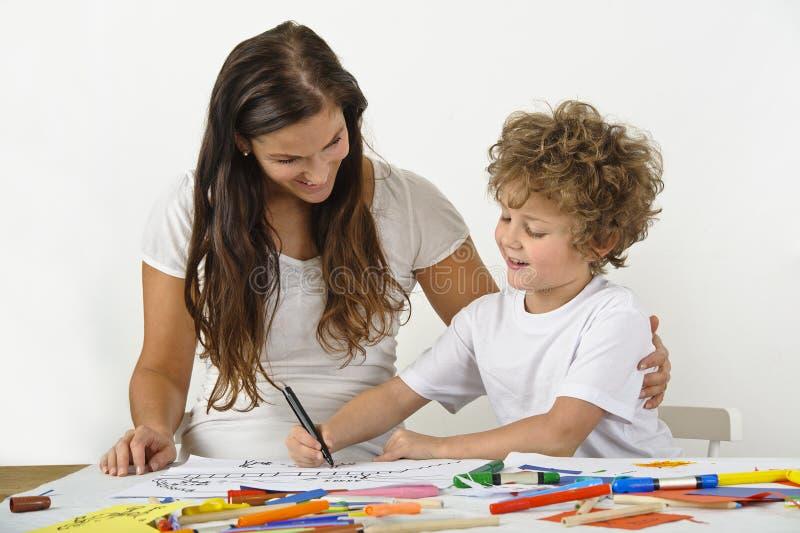La mujer enseña su niño a cómo dibujar foto de archivo
