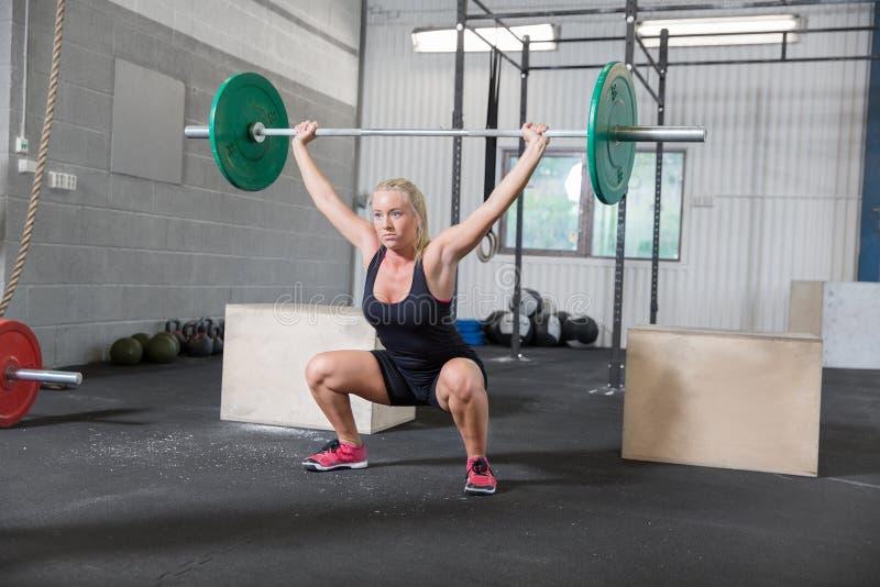 La mujer entrena a posiciones en cuclillas en el centro del crossfit fotografía de archivo libre de regalías