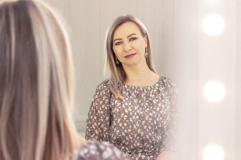 La mujer envejeció miradas en el espejo Reflexi?n en el espejo Edad mayor foto de archivo libre de regalías