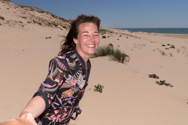 La mujer envejecida media feliz del hombre se junta en las manos de la playa junta fotos de archivo libres de regalías
