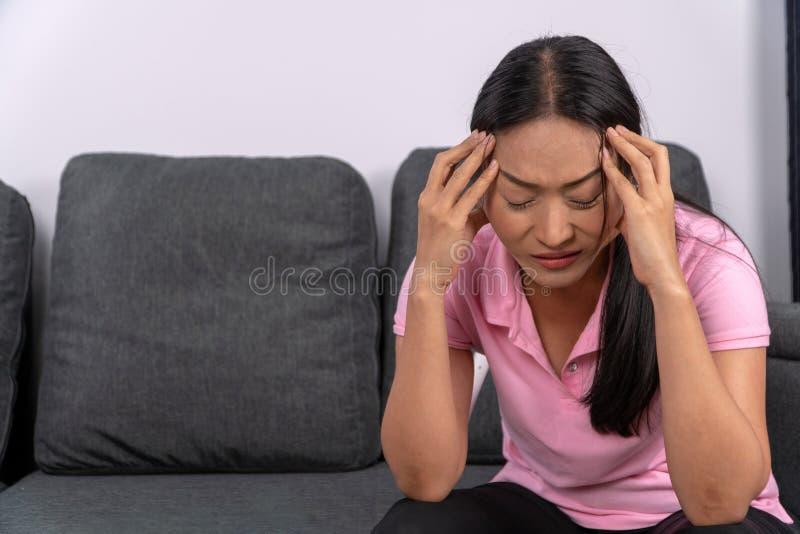La mujer envejecida media se sentaba en el sofá y llevaba a cabo su cabeza debido a stress laboral Y problemas económicos foto de archivo libre de regalías