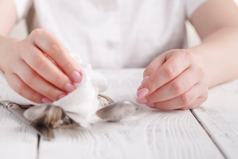 La mujer es de limpieza y de secado de las cucharas para abastecer fotografía de archivo
