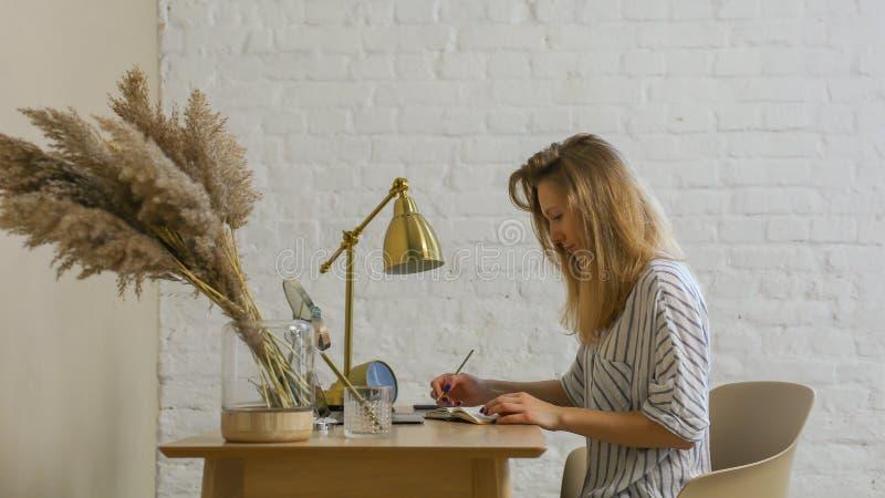 La mujer es escritura en la tabla fotos de archivo libres de regalías