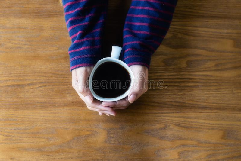 La mujer es manos que sostienen el café de la taza, visión superior, madera fotos de archivo