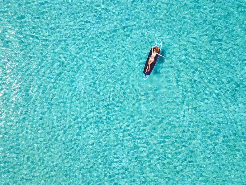 La mujer es relajante en una tabla hawaiana sobre las aguas tropicales imagenes de archivo