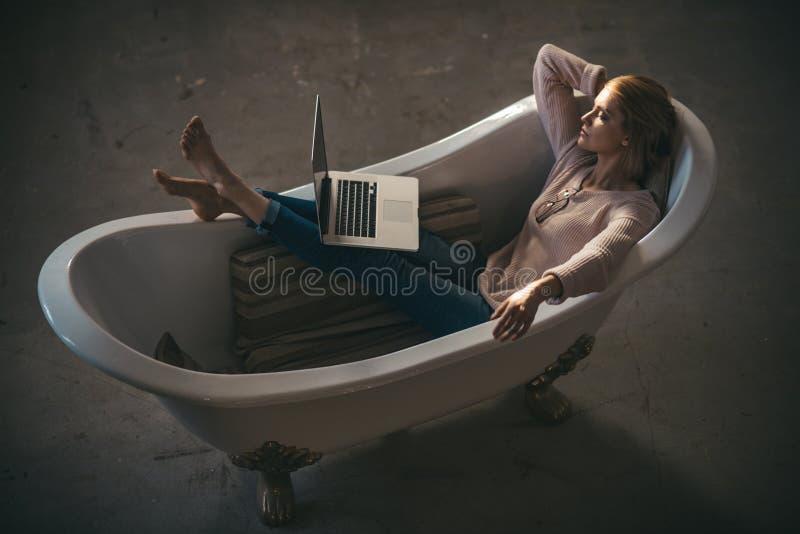 La mujer es relajante y con el ordenador portátil en casa Mujer rubia atractiva que mecanografía en el ordenador portátil en baño fotografía de archivo