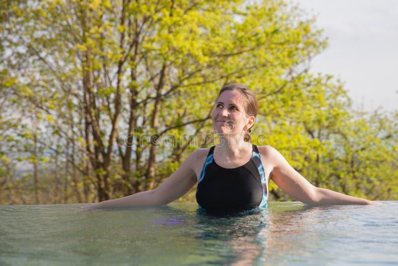 La mujer es restos en piscina al aire libre fotografía de archivo libre de regalías