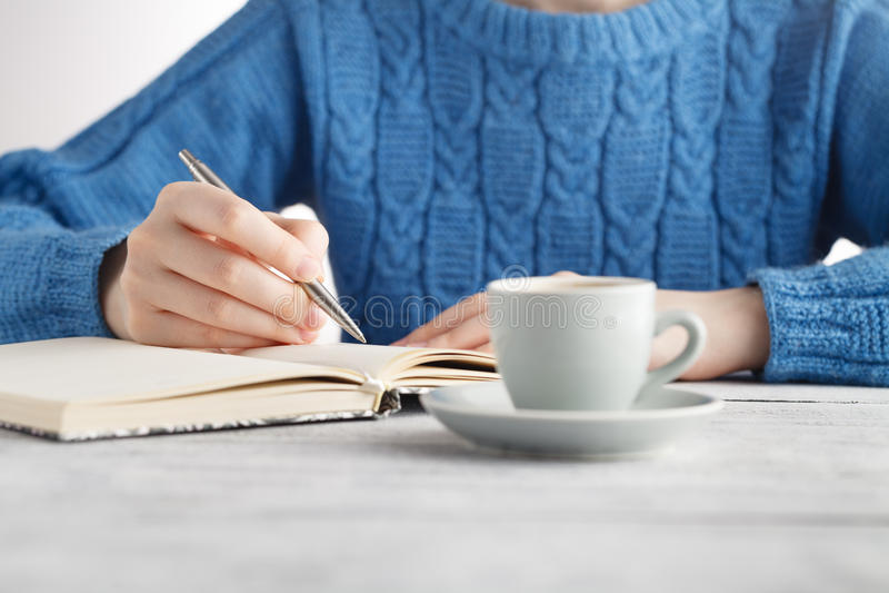 La mujer escribe en cuaderno y bebe el café imagen de archivo
