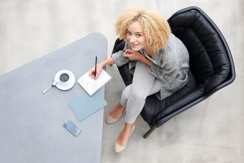 La mujer escribe en un cuaderno imagen de archivo libre de regalías