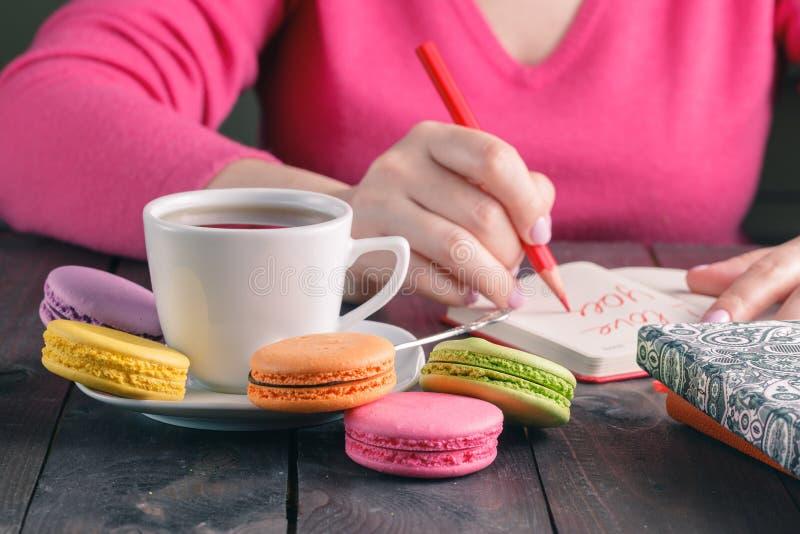 La mujer escribe la letra te quiero mientras que bebe el café fotografía de archivo libre de regalías