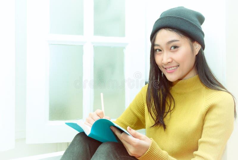 La mujer escribe las notas cerca de la ventana, forma de vida relajante imagenes de archivo
