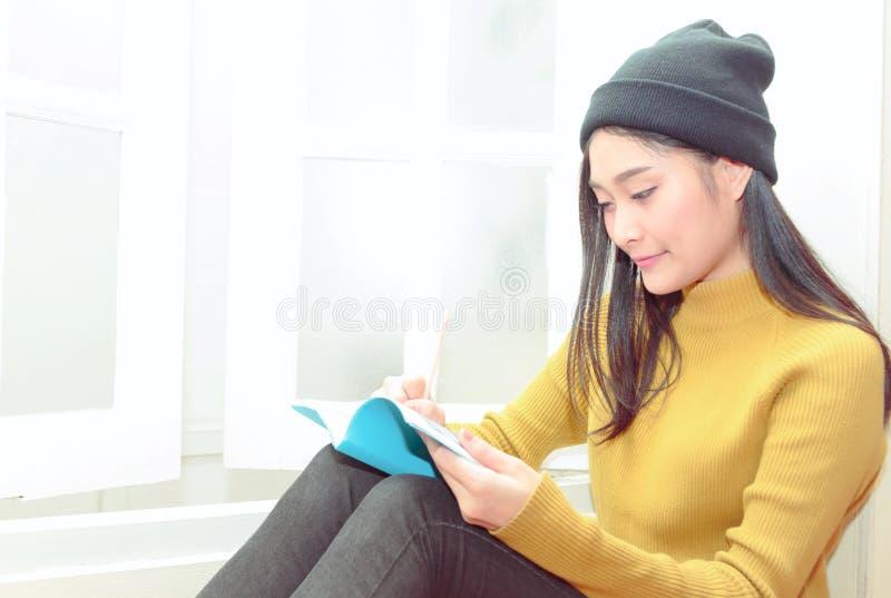La mujer escribe las notas cerca de la ventana, forma de vida relajante imagen de archivo libre de regalías