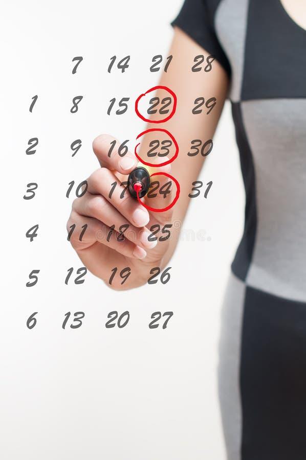 La mujer escribe los días en el calendario fotos de archivo