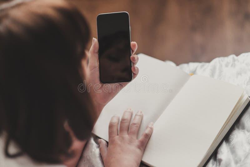 La mujer escribe SMS en smartphone en la camiseta blanca y azul hermosos imágenes de archivo libres de regalías
