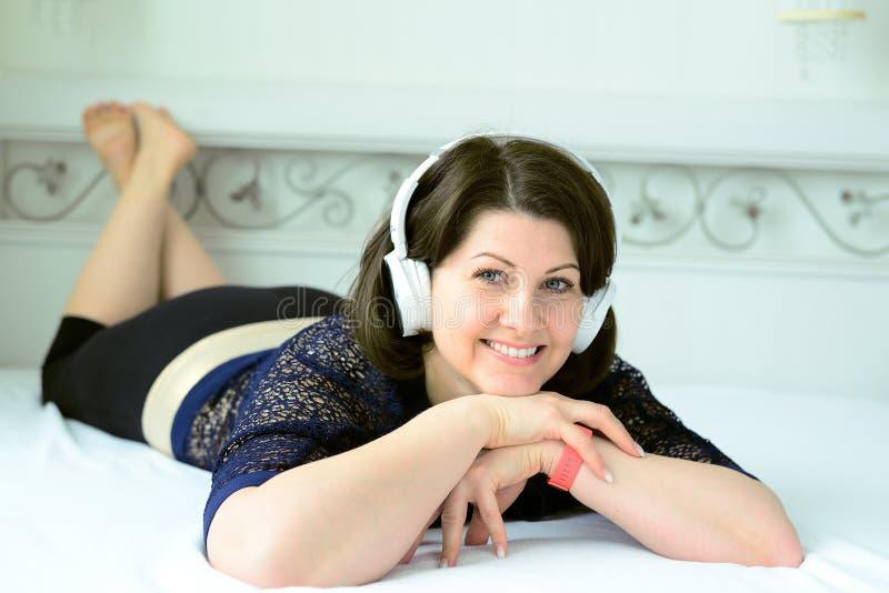 la mujer escucha la música en los auriculares y miente en cama fotos de archivo
