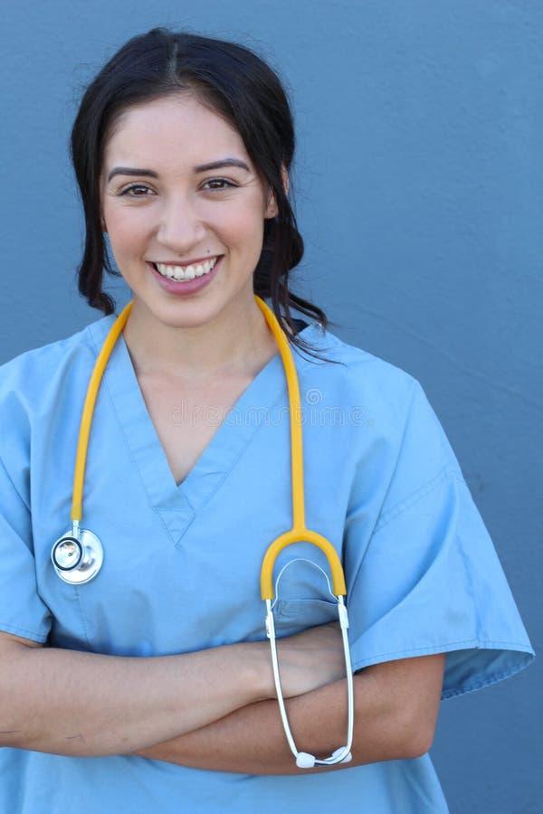 La mujer española morena del doctor con sus brazos cruzó la sonrisa aislada en fondo azul imagen de archivo libre de regalías