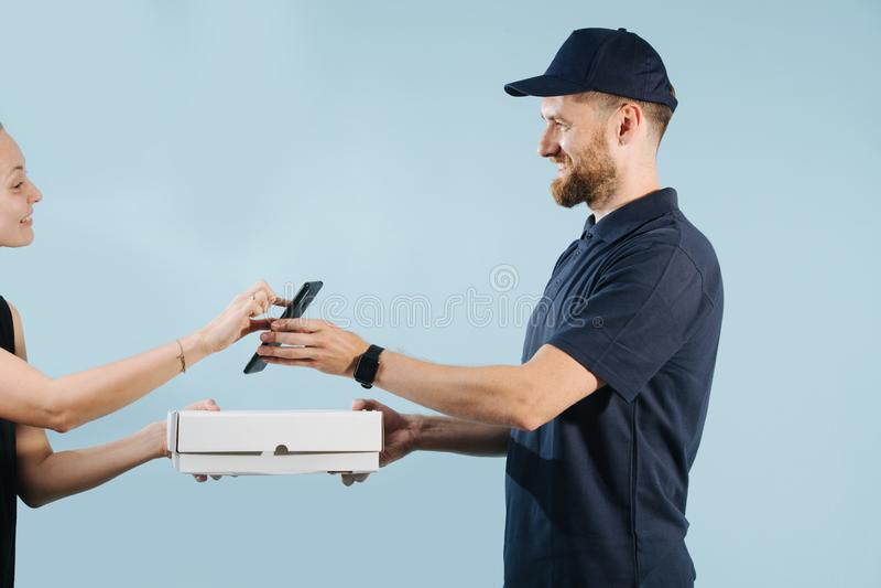 La mujer está aceptando una entrega de la caja de un mensajero firmando en un teléfono elegante fotografía de archivo libre de regalías