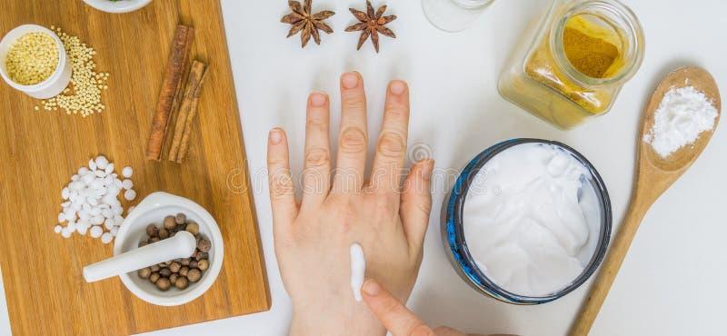La mujer está aplicando la crema hecha en casa a mano Muchos ingredientes en fondo imagenes de archivo