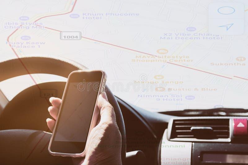 La mujer está conduciendo peligroso el coche mientras que sostiene y mira un mapa fotografía de archivo libre de regalías