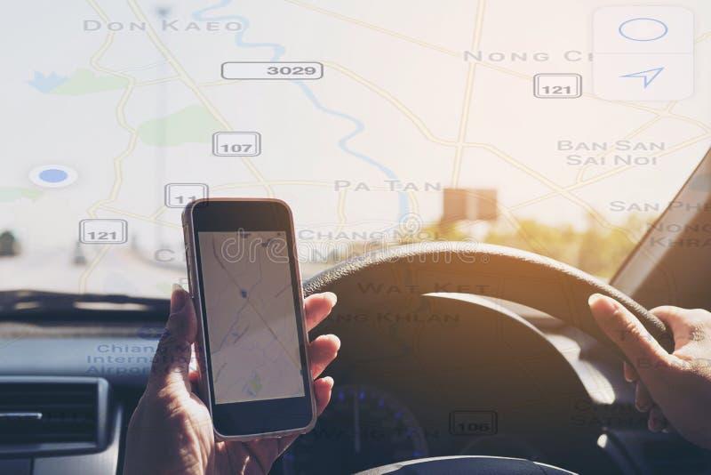 La mujer está conduciendo peligroso el coche mientras que sostiene y mira un mapa fotos de archivo libres de regalías