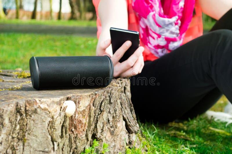 La mujer está conectando su smartphone con el altavoz inalámbrico fotos de archivo