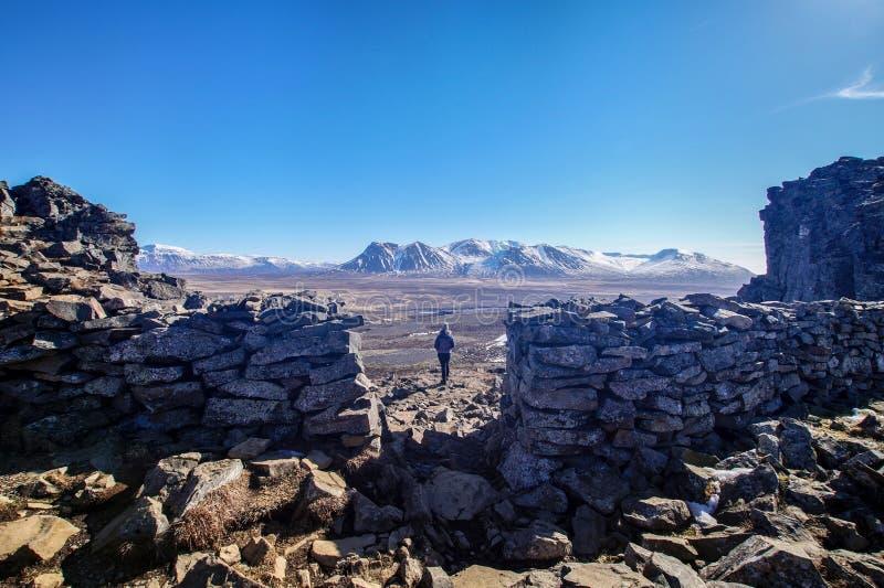 La mujer est? disfrutando de la visi?n desde las ruinas de la fortaleza Borgarvirki de vikingo en Islandia foto de archivo